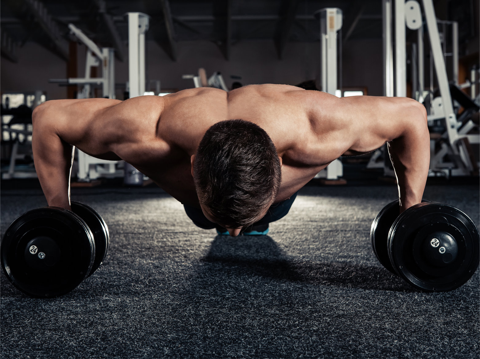 Handsome muscular man doing pushup exercise with dumbbell